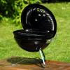 Weber barbecue op een tafeltje met gras op de achtergrond